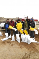 Workers making sandbags to protect from flooding.
